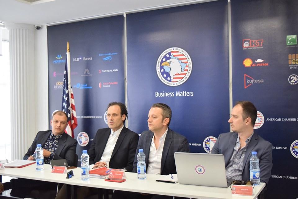 katër burra gjatë një diskutimi në panel