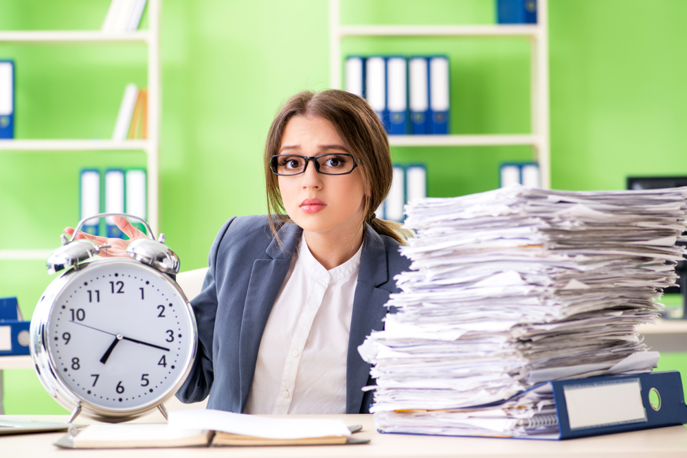 woman in business suit looking concerned and sitting on chair front of desk with a lot of paperwork and a round analog clock