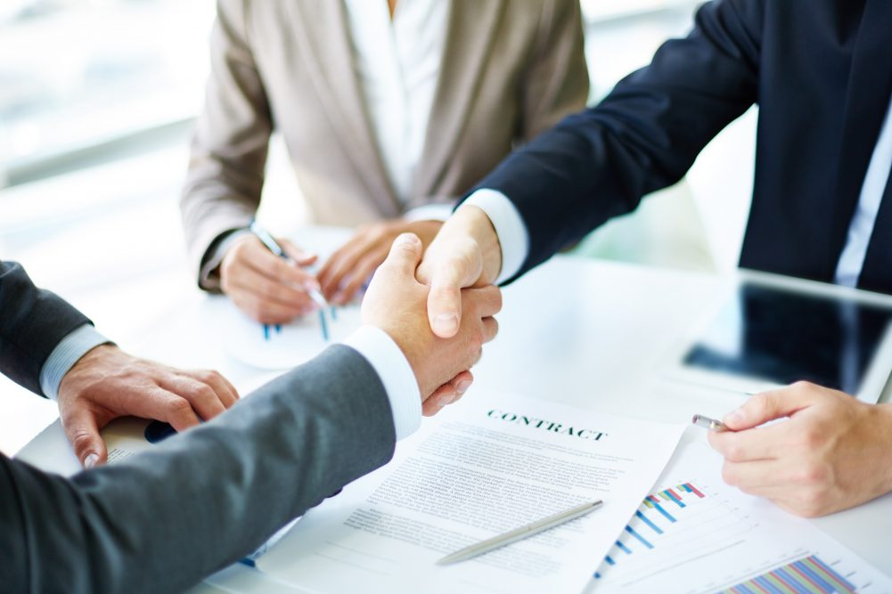 two men shaking hands and agreeing on a deal